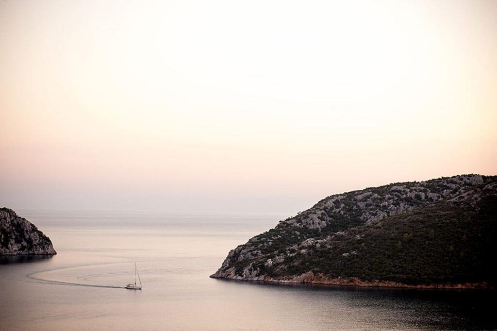 Beaches of Sithonia - A fishing boat enters Porto Koufo, Greece's largest natural harbor